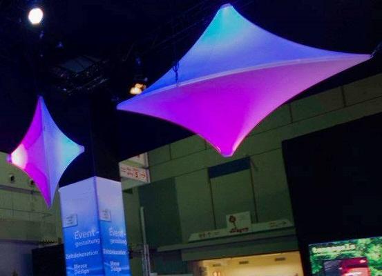 Agentur Rindle blau und lila oder violett beleuchtete Raumskulptur hängend vor schwarzem Hintergrung Kreiselform Messestand Säule Column im HintergrundDouble Spin hms