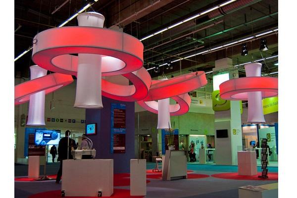 Agentur Rindle fliegender oder hängender easy donut Ring aus Aluminium und Stretchstoff mit roter Beleuchtung in Kombination mit Column in einer Ausstellungshalle oder einem Messestandals Eyecatcher hms
