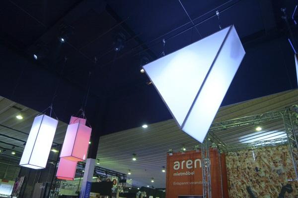 Agentur Rindle blaue Raumskulptur in From eines Dreiecks und cubes vor schwarzem Hintergund auf Messegelände geometrische Dekoration in Eingangsbereich oder als bedruckte Werbetafel stehend und hängend einsetzbar hms