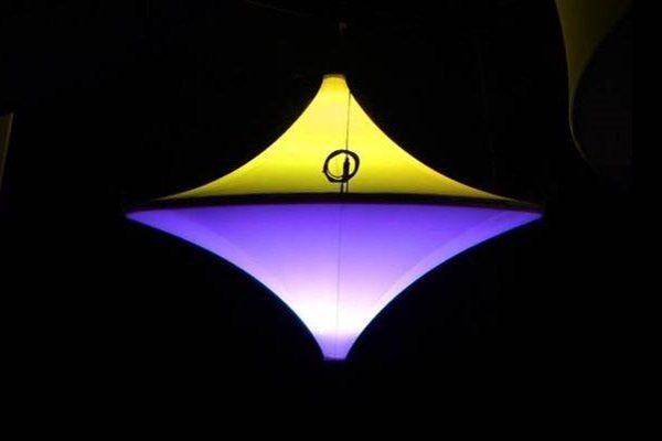 Agentur Rindle blau und gelb beleuchtete Raumskulptur hängend vor schwarzem Hintergrung Kreiselform Messestand Double Spin hms