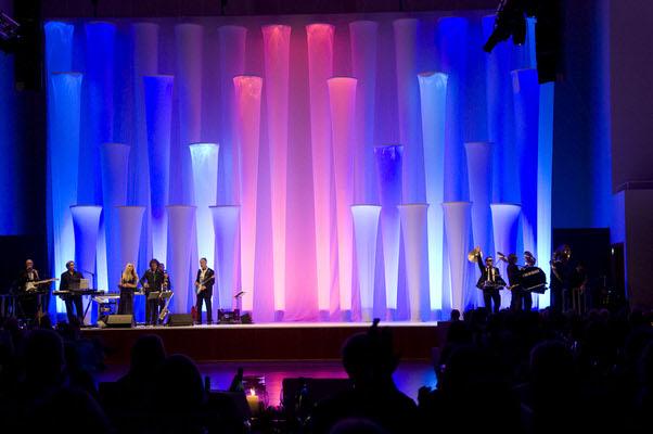Bühnendekoration aus den Säulen der Helsinki-Serie, rot und blau beleuchtet Helsinki A Helsinki B und Helsinki C sind aufhängbare Säulen, die miteinander kombinierbar sind und aus einer Aluminiumkonstruktion bestehen, die mit StretchStoff bezogen wird